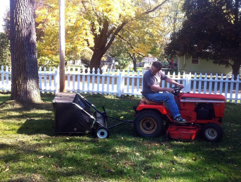 A man in a lawn with lawn sweeper
