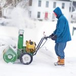 Man in a blue jacket with a snow blower