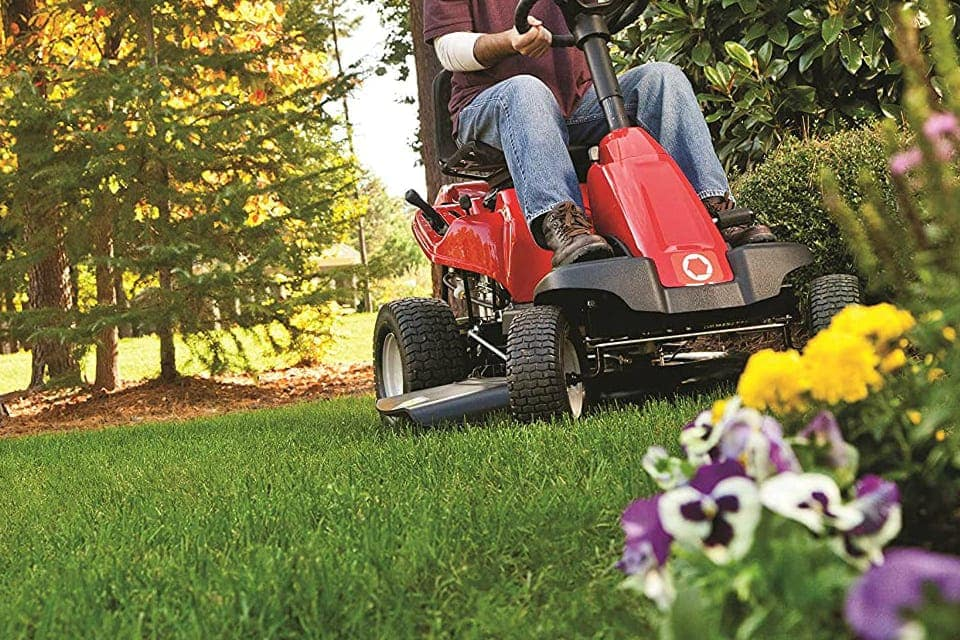 a man with a red riding lawn mower