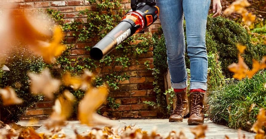 Woman using a leaf blower in the garden